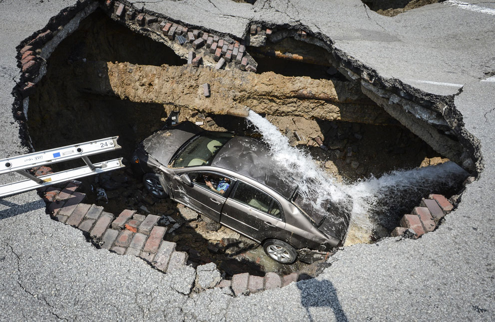 A car at the bottom of a sinkhole caused by a broken water line in Toledo, Ohio on July 3, 2013. Police say the driver, 60-year-old Pamela Knox of Toledo, was shaken up and didn't appear hurt but was taken to a hospital as a precaution. Fire officials told a local TV station that a water main break caused the large hole. (AP Photo/Lt. Matthew Hertzfeld, Toledo Fire and Rescue)