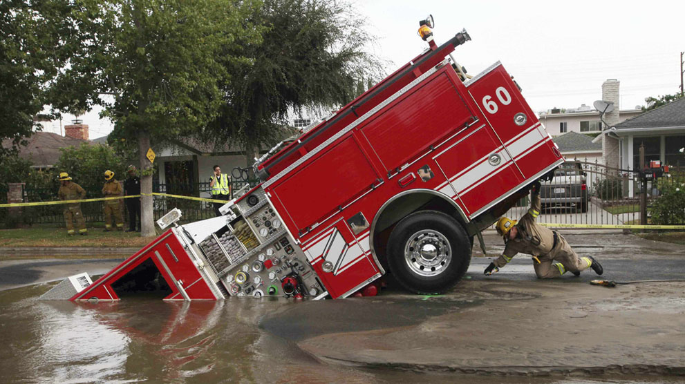 A Los Angeles fireman looks under a fire truck stuck in a sinkhole in the Valley Village neighborhood of Los Angeles, on September 8, 2009. Four firefighters escaped injury early Tuesday after their fire engine sunk into a large hole caused by a burst water main in the San Fernando Valley, authorities said.