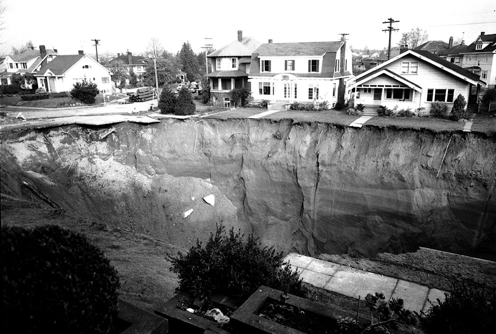 On the night of November 11, 1957, a huge hole opened up in Seattle's Ravenna neighborhood, caused by the failure of an underlying six-foot diameter sewer pipe. The 60-foot-deep hole affected only the streets, sidewalks and some yards, as seen in this photo taken at 16th Ave. NE and Ravenna Blvd on November 15, 1957. No homes were damaged, and nobody was injured, but the hole took two years to fill and repair. More on the story here. Also, see this intersection today on Google Maps Street View. (Courtesy Seattle Municipal Archives)