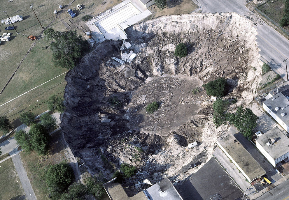 This aerial view shows a large sinkhole that claimed several sports cars, a house, and the deep end of the city swimming pool, in Winter Park, Florida, on May 11, 1981.