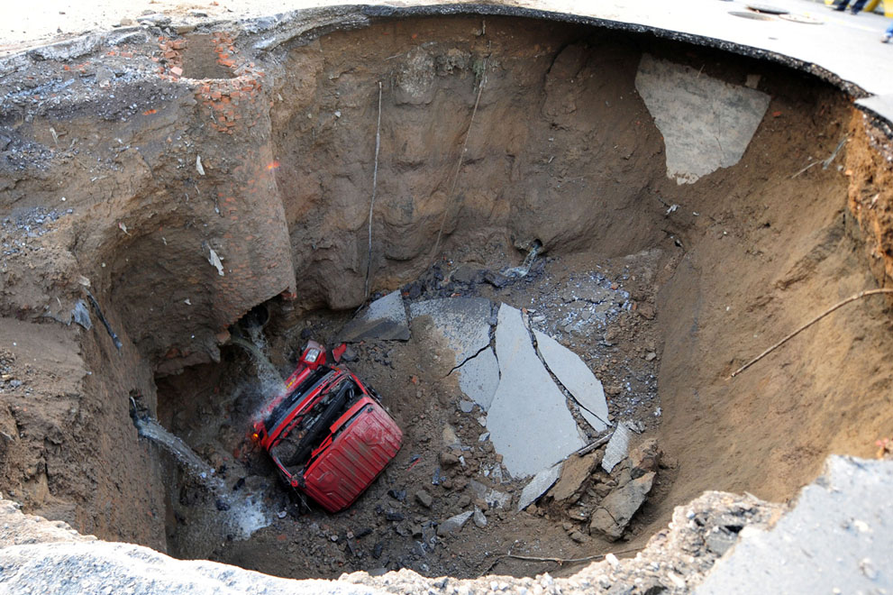 A truck lies in a sinkhole which occurred overnight on Shiliuzhuang road, in Beijing, on April 26, 2011. A section of the road collapsed beneath the truck, slightly injuring the driver and a passenger, who both jumped out the vehicle before it sank into the hole.