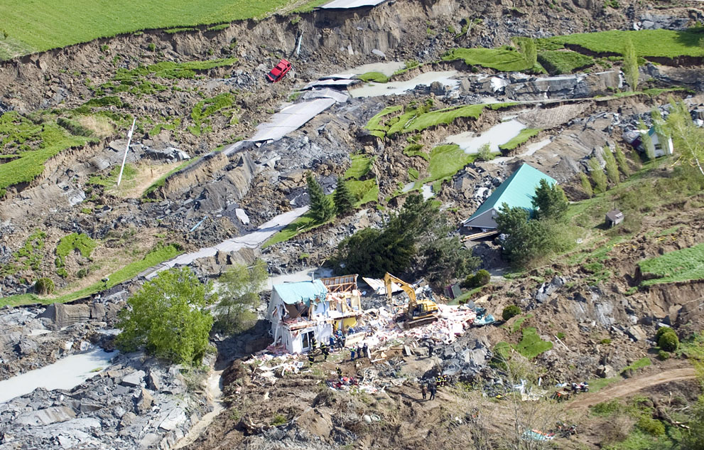 Rescuers work at the scene of a landslide in Saint-Jude, Quebec as shown from the air on Tuesday, May 11, 2010. Four people, including two children, are missing after a sinkhole triggered by a landslide swallowed their house northeast of Montreal.