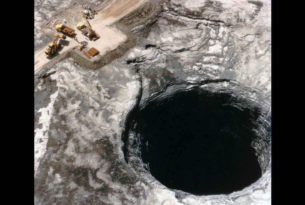 In June of 1994, a huge hole, 106 ft. wide by 185 ft. deep, opened in the center of an IMC-Agrico waste stack near Mulberry, Florida. The sinkhole, shown in this July 13, 1994 photo, released 20.8 million pounds of liquid phosphoric acid into the ground below, and into the Floridan aquifer, which provides 90 percent of the state's drinking water. The company voluntarily spent .8 million to plug the sinkhole and control the spread of contaminants in the ground water.