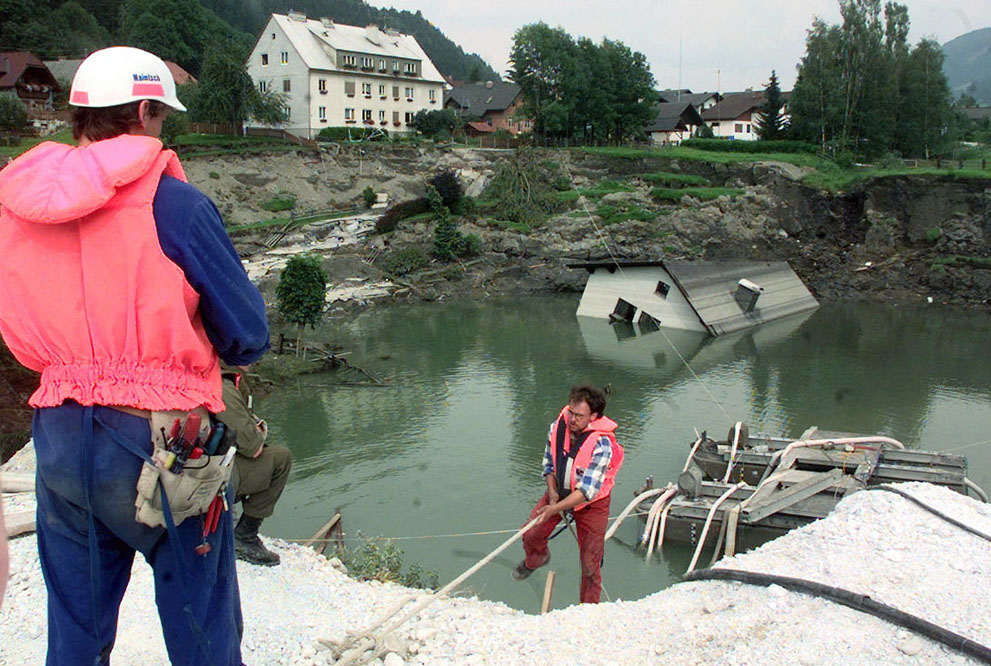 The Lassing mining disaster. On July 17, 1998 a Talc mine below the town of Lassing, Austria, experienced a partial collapse, filling with groundwater and opening up a sinkhole in the town above. Shortly after, a rescue crew of 10 men went into the mine to search for a single missing miner, and a massive collapse followed, opening up an even larger crater above. The first missing miner was found alive after ten days, but all ten of the rescue team members were killed. Here, workers examine the crater, on July 22, 1998.