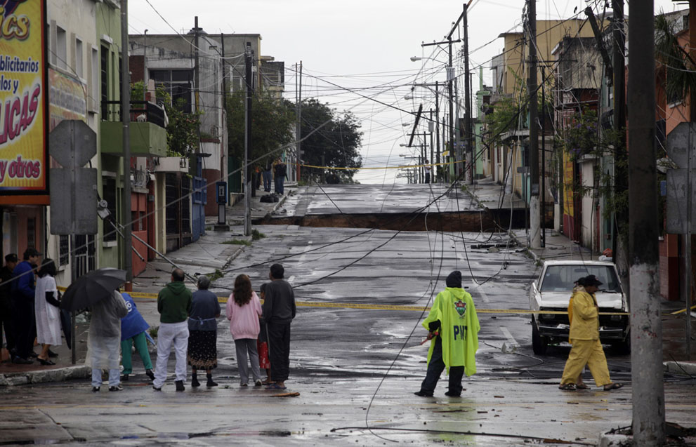 Neighbors gather near the site of a huge sinkhole in Guatemala City, on May 30, 2010.