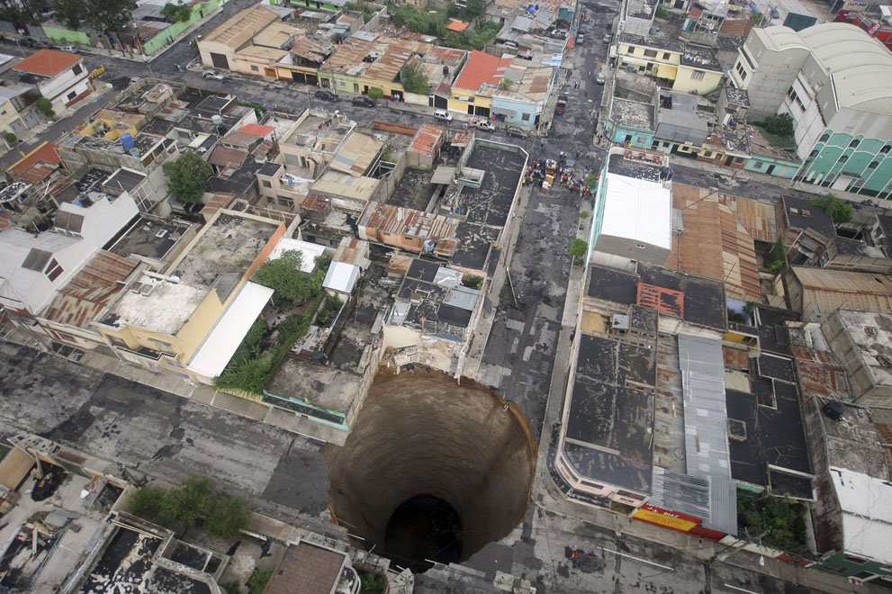 A giant sinkhole in Guatemala City, on May 31, 2010. More than 94,000 were evacuated as the storm buried homes under mud, swept away a highway bridge near Guatemala City and opened up several sinkholes in the capital.