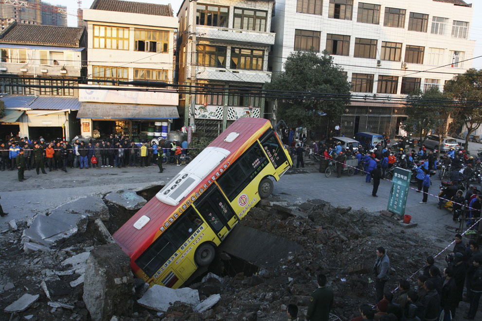 A bus, after falling into a pit created by an underground explosion in Rui'an, Zhejiang province, on January 16, 2011. An explosion on a road in east China's Zhejiang Province tossed a bus without passengers four meters into the air, injuring the driver and a 6-year-old boy on the roadside, local fire fighters said on Sunday. The cause of the explosion was under investigation, Xinhua News Agency reported.