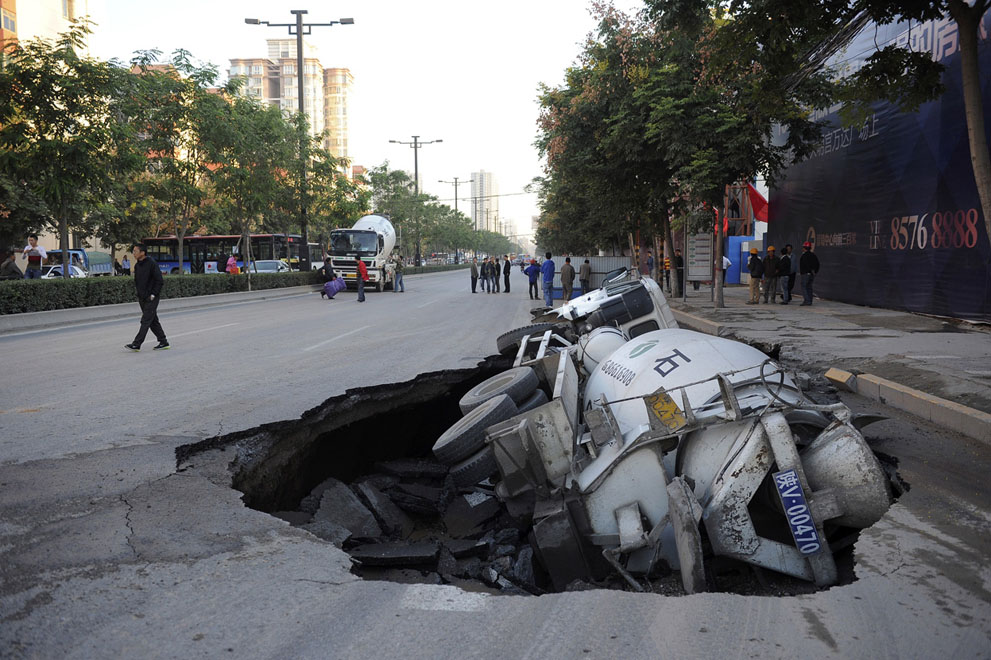 A man walks past a cement truck which fell into a pit after the road caved in, in Xi'an, Shaanxi province, on September 28, 2012.