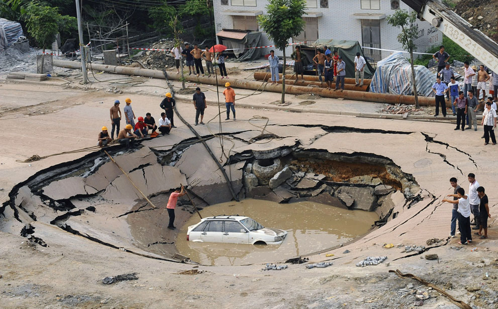 A stranded car is hoisted from a collapsed road surface in Guangzhou, Guangdong province, on September 7, 2008.