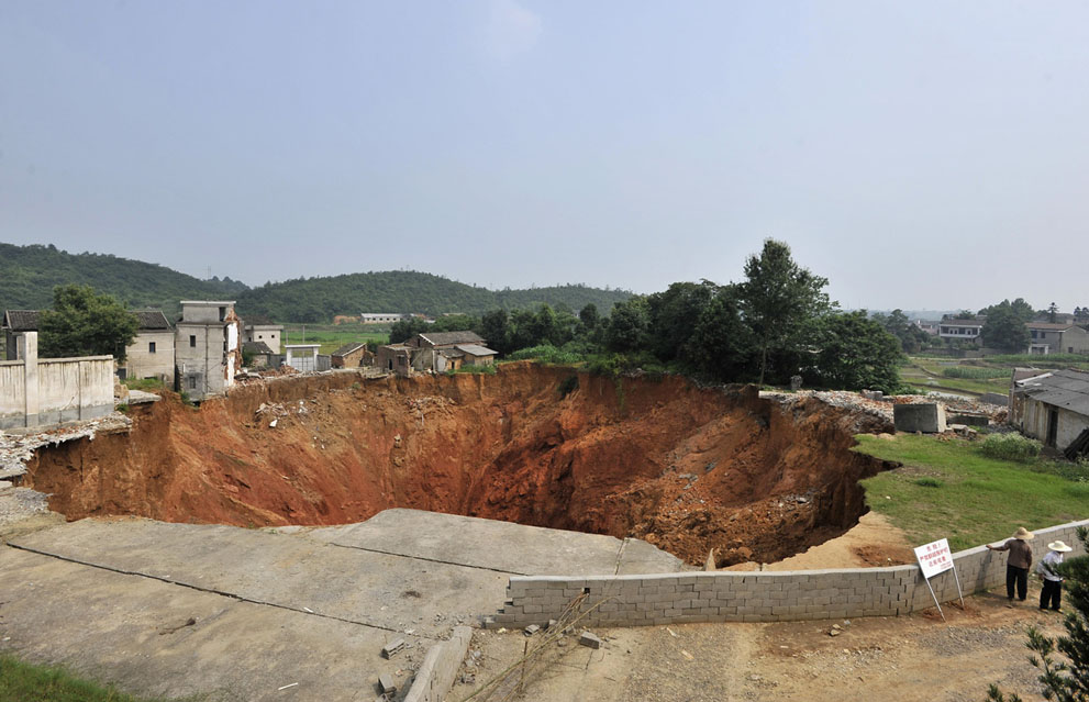 Local residents look at a sinkhole near Qingquan primary school in Dachegnqiao town of Ningxiang, Hunan province, on June 15, 2010. The hole, 150 meters (492 feet) wide and 50 meters (164 feet) deep, first appeared in January and has destroyed 20 houses so far.